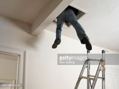 foto de stock man dangling out of loft hatch with one foot touching step ladder