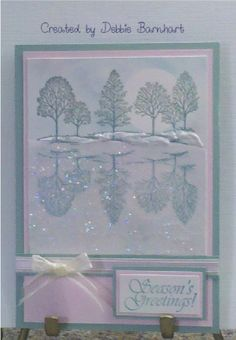 the reflection is stamped on vellum then flipped so it is a mirror image of the top one. Under the top trees used Liquid Pearl in white to make it look like snow. To make the bottom look like water, covered the area with vellum adhesive and sprinkled it with fine clear glitter - bjl