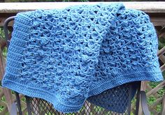 This lacy throw looks classy in a solid color, but can be made with stripes. The example is made in worsted weight acrylic yarn.