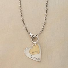 "Love Mom Necklace Item No. 65243	 $188.00 Two hearts with a hand stamped message of love for mom. ""LOVE"" heart, chain and lobster clasp are sterling silver; ""MOM"" heart is bronze. Ours exclusively, handmade in USA. 18""L."