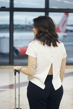 Look aeroporto calça de moletom preta, camiseta branca, jaqueta floral, bolsa Louis Vuitton, pompom, tênis New Balance marrom.