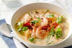 stoofpot - scampi's, basmatirijst, ... - Verhit wat olie in een wok. Voeg de currypasta toe en roerbak 2 minuten, tot de geuren vrijkomen. Voeg de knoflook en de gember toe, bak nog even mee. Schenk er de bouillon en de kokosmelk bij. Breng aan de kook.