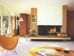 Mid Century Modern: Fantastic image of the interior of a 1950's home. Large floor the ceiling windows with full length curtains. Colour scheme is all yellows and oranges and browns. The brick cladding feature around the fireplace. The rounded furniture pieces. Very warm and inviting while still having the clean lines and uncluttered surfaces.