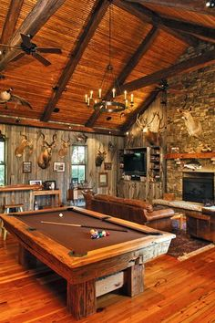 Game Room with rustic styled wood paneled walls, ceiling and beaming and stone fireplace | Phillip W Smith portfolio