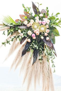 Poolside boho wedding ceremony arbour with pampas grass, proteas, peonies and spray painted foliage | Andrew Clifforth Photography