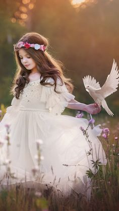 Children's outdoor photography, pretty young girl with white dress and flower crown, with bird on her hand