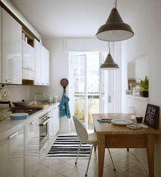 tipica cucina lunga e stretta col balcone alla fine; bianco, tavolo in legno, da notare i due lampadari grandi e la nicchia/mensola