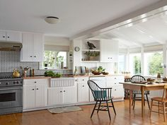 A 1950s Fishing Shack Transforms Into a Charming Home-The Kuykendalls painted the blah beige fronts of their cabinets with the same bright white they used throughout the rest of the 1,500-square-foot house. Cast-iron knobs from House of Antique Hardware and a new butcher-block countertop finish off the simple cabinetry. Having saved by sprucing up (instead of ripping out) the original cabinetry, Bonnie splurged on a porcelain apron-front sink from Whitehaus Collection.