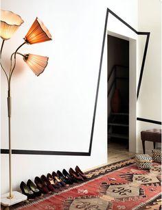 Peinture salon murs blanc, lignes graphiques noires sur mur et encadrement porte. au sol un tapis Kilim rouge en contraste