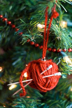 "Easy knitting ball ornament--made from de-umbrella'd drink umbrellas for the ""needles"" and a ball of yarn.  Could glue and wrap around a styro ball or glass ornament.  Too cute for the knitters in your life."
