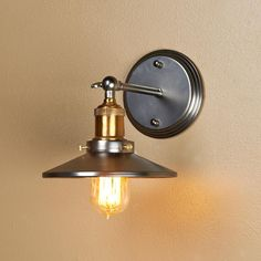 Mirror Lined Cone Shade Wall Sconce Faceted mirror lined shade and historical fittings reflect a vintage vibe. Brass medium base socket with pewter shade and backplate. 60 watts.