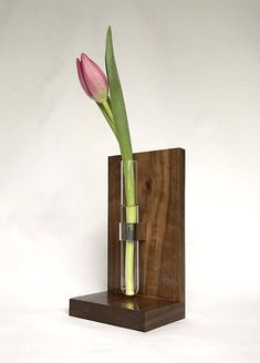 This minimal modern table bud vase gives an accent to your home or office. * It is constructed out of solid walnut, stainless steel and glass (test tube). * Wood is sanded and clear coated. * Overall Product Size : 7 1/4 x 4 x 3 (18.5 cm x 10 cm x 8 cm) * Test tube: 5 7/8 (15 cm)