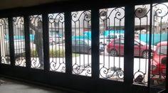 Portón de hierro forjado con portigos de vidrio en garage cerrado