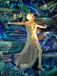 The fish were made by artist Brett Windham using mosaic tile, and rhinestones, gems, and sequins. The mannequin is wearing an outfit from the Alexander McQueen Spring 2012 collection.     A Bergdorf Goodman Christmas window display in the Carnival of the Animals series.