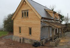 Oak framed house with SIPS log store lean to