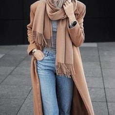 Pair a tan coat with light blue jeans for a casual level of dress.   Shop this look on Lookastic: https://lookastic.com/women/looks/camel-coat-grey-long-sleeve-t-shirt-light-blue-jeans/16189   — Tan Scarf  — Grey Long Sleeve T-shirt  — Camel Coat  — Light Blue Jeans