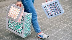 Cropped shot of a women carrying three patterned bags