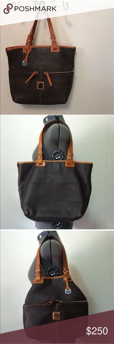 """Dooney & Bourke Tote Bag Authentic Dooney & Bourke brown leather w/ honey colored handles and edging. Hang Tag was not bought with bag but matches perfect and will come with the bag. Has yellow reg. card and stickers are still inside the pocket. Bag has been registered. Will come with a dust bag. Snap closure.Can be used two different ways. B62817/T, C  Condition - great condition, only signs of use are on corners.   Color - brown,tan  Measurements -  16""""W x 12""""H x 4.75""""D 9"""" strap drop…"""
