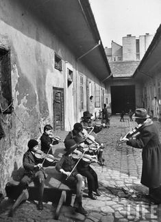 Gypsy children being taught to play the violin in a courtyard of one of the poorer houses (Budapest, Hungary 1939.) Photo by William Vandivert