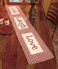 An uplifting message accompanies your table settings with a Live-Laugh-Love Table Runner. The traditional checkered pattern goes with almost any kitchen or dini