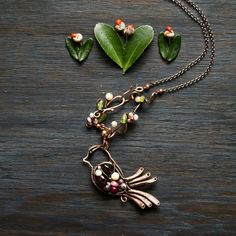 Long necklace with paradise bird pendant. Made with January birthstone garnet.