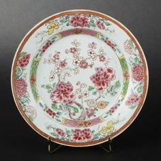 Compagnie des Indes porcelain plate with peony branches and blossoming apple trees decoration  China Compagnie des Indes porcelain plates decorated with famille rose enamels. Outer rim and center with peony branches and blossoming apple trees decoration. Inner rim containing four reserves with peonies against a checkered ground.Qianlong Period, circa 1740