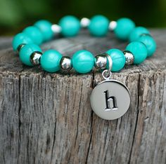 Soft silicone beads strung with alternating silver 6mm beads and silver initial charm. Please type the initial that you would like in the text box above.