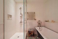 Señorial - AD España, © blocksy.com En el baño: gran bañera, ducha independiente y calentador de toallas sobre un suelo de mosaico hidráulico personalizado.