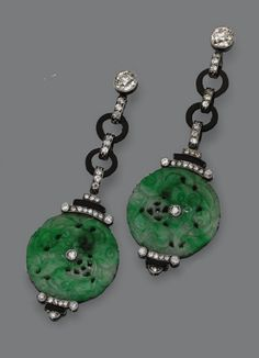 Pair of Art Deco Jade, Onyx and Diamond Earrings, circa 1925. Designed as fringes of diamond-set links and onyx rings supporting 2 carved and pierced jade discs, the whole set with 56 old European-cut diamonds weighing approximately 1.35 carats and 2 rose-cut diamonds, mounted in platinum. #ArtDeco #earrings