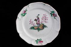 Assiette à bord lobé à décor polychrome d'un chinois debout sur une terrasse fleurie, tenant un plat rempli de fruits en offrande. Trois tiges fleuries sur l'aile. Lunéville, Fin XVIII°S. D : 24,5 cm