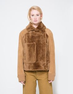 From Tibi, a contemporary aviator jacket in Bear Brown. Wide, pointed collar. Removable neck latch. Concealed front snap closure. Front patch pockets with top and side entry. Gold-tone hardware. Ribbed cuffs. Allover shearling with soft suede reverse.