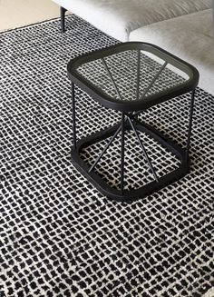 Woodnotes' black Twiggy table size 44x44x45,5 cm together with Grid han knotted wool carpet col. white-black.