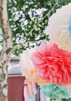 Tissue-Paper Pom-Poms  Pom-poms, strung inside your tent, hung from chairs, or even tucked into vases, are a fun (cheap!) way to give your space a dash of color. Of course, this look is perfect for a laid-back outdoor wedding; but we've seen it work for more formal weddings too (with, for example, eggplant-colored tissue-paper pom-poms clustered together to create eye-catching decor).
