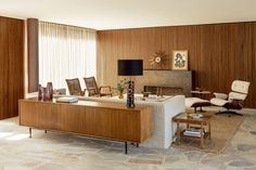 The living area walls are sheathed in the same Brazilian walnut used for the exterior of the house. A Murano-glass lamp sits atop a credenza designed by Obra Prima, the Eames lounge chair and ottoman are by Herman Miller, and the armchairs are vintage; the fireplace surround is crafted of steel. - photo: Ricardo Labougle