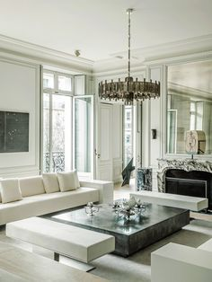 In the living room, a Mathieu Lustrerie chandelier hangs above sofas designed by Dirand as an homage to Eileen Gray. On the wall is a 1975 work by Alighiero Boetti.