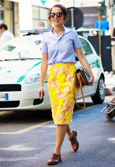 A blue button-down shirt is worn with a yellow pencil skirt, a brown leather bag, brown oxfords, and sunglasses