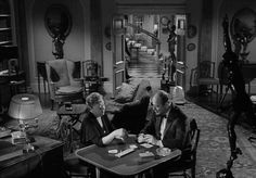 Julian Karswell (Niall MacGinnis) at home playing cards with his mother(Athene Seyler), when they here someone knocking at the door - Night of the Demon (1957)