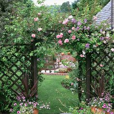 Courtyard of this country garden is framed by a pergola, cloaked in roses and clematis. Planters filled with brightly coloured flowers add even more interest to this welcoming entrance arch. Just lovely!!