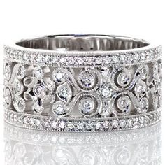 Caledonia Petite - Caledonia Petite is a brilliant display of pierced filigree scrolls and micro pavé diamonds. The wide 14k white gold band presents a significant display with two outer bands of round cut micro pavé diamonds. Within the bands, the open spaces and milgrain edging highlight the filigree design.