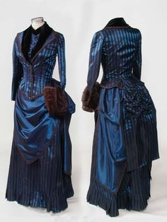 1883 day dress ensemble: blue/black striped bodice with velvet trim and tails, over a draped bustle skirt.  Underneath a bustle pad and petticoat w/ruffles down the back.  from:  http://www.knowlesville.com