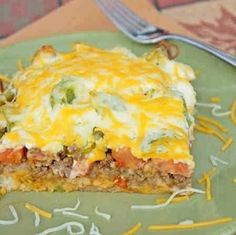 Ingredients : 2 pounds ground beef, cooked and drained 1 (1.25-ounce) packet taco seasoning 4 ounces sour cream 4 ounces mayonnaise 8 ounces Cheddar cheese, shredded and divided 1 yellow onion, sliced 2 cups biscuit mix 2 tomatoes, sliced 1 green bell pepper, sliced 1