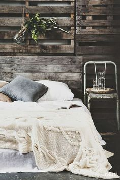 The delicate bed-cover contrast beautifully with the rough pallet walls in this rustic bedroom