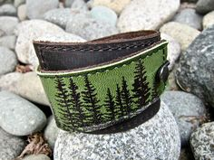 "$27.00 I've made this wrapping cuff out of soft, scuffy brown and green leather. The leather has been hand printed with artwork using indelible (permanent) ink. Machine stitched, it has an attached elastic that hooks over a button, so this cuff will adjust to fit most wrist sizes 5.75"" to 7"" in circumference. At the narrowest, the width of the cuff is 1.25"" and at the widest it's 2"". Leather Cuff Bracelet Wrap Wilderness Pine Print in by Hollyhawk"