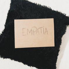 Foto de um cartão em papel pardo escrito empatia em cima de uma almofada preta com pelos