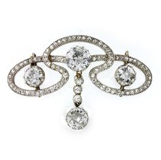 Edwardian diamond scroll brooch, the brooch comprising three old brilliant-cut diamonds, within a flowing openwork diamond-set scroll surround, with old brilliant-cut diamond drop to the centre, the diamonds estimated to weigh a total of 3.2 carats, all set in silver with grain edging to a yellow gold mount and brooch fitting, gross weight 7.1 grams, circa 1900