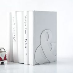 White metal holder for book with an ampersand shape