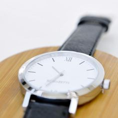 Minimalistic silver watch with stainless steel case and eggshell face. Sustainable black textured leather band meticulously crafted from surplus scrap leather that would have otherwise gone to waste. Leather Scraps, Watch Faces, Silver Rounds, Egg Shells, Stainless Steel Case, Quartz, Black Leather, Band, The Originals