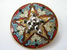 the most beautiful button I've ever seen:  a Victorian enameled pierced brass button with cut steel rivets