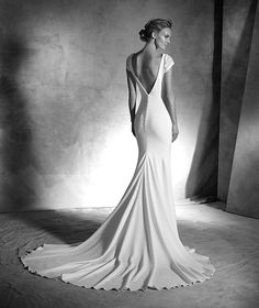 IRUNE style: Mermaid wedding dress in crepe. Bodice with short puffed sleeves decorated with gemstones. Plunging V-back with covered buttons.