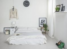 Minimalist white bedroom design with floor bed and smal wooden side table also lovely small veiled lamp on the white storage boxes decorated by candles and green plants Matress On Floor Ideas, Mattress On Floor, Bed On Floor, White Bedroom Chair, White Bedroom Design, Diy Home Decor Bedroom, Small Room Bedroom, Decor Room, Minamilist Bedroom
